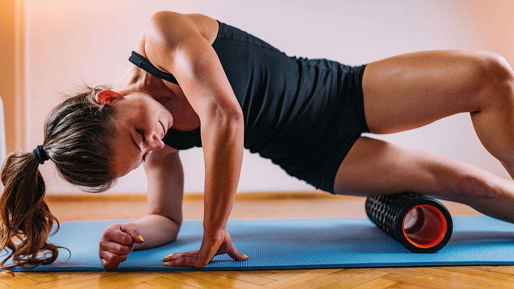 Faszien Training mit einer Faszienrolle an den Beinen