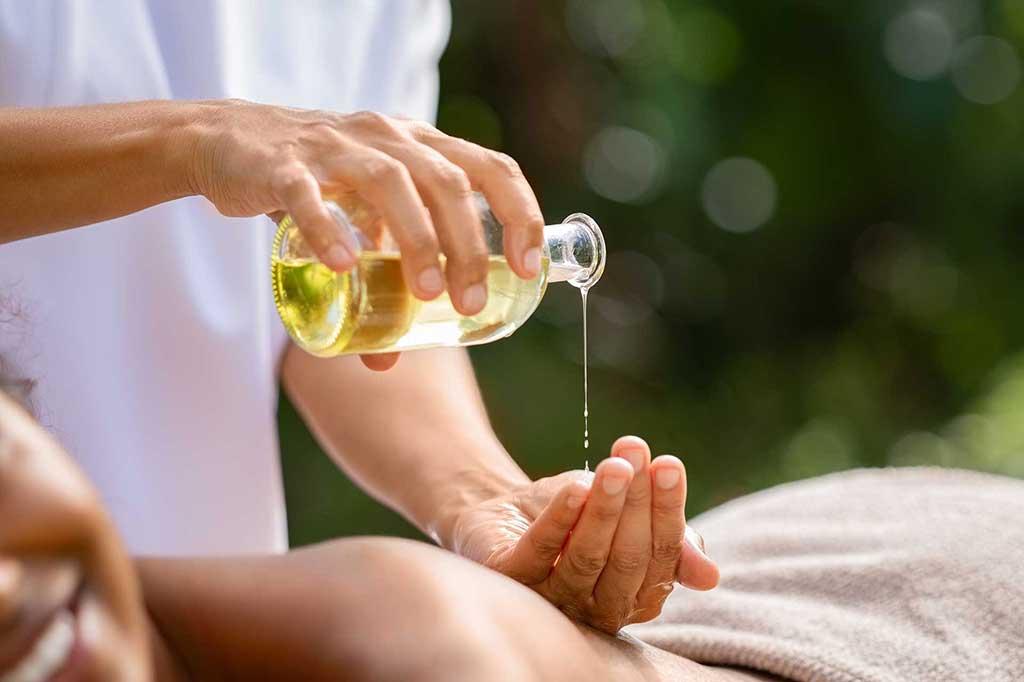 Aroma-Massage mit Massageöl - Masseuse bedeckt ihre Hand mit Massageöl aus einer Flasche