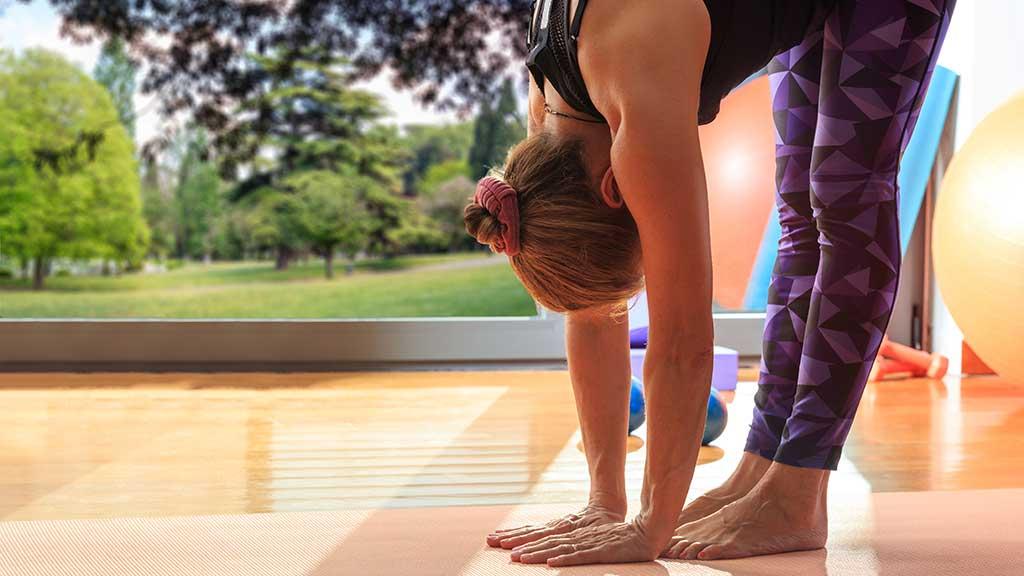 Frau macht bei einer Pilates Übung die Hände auf den Boden