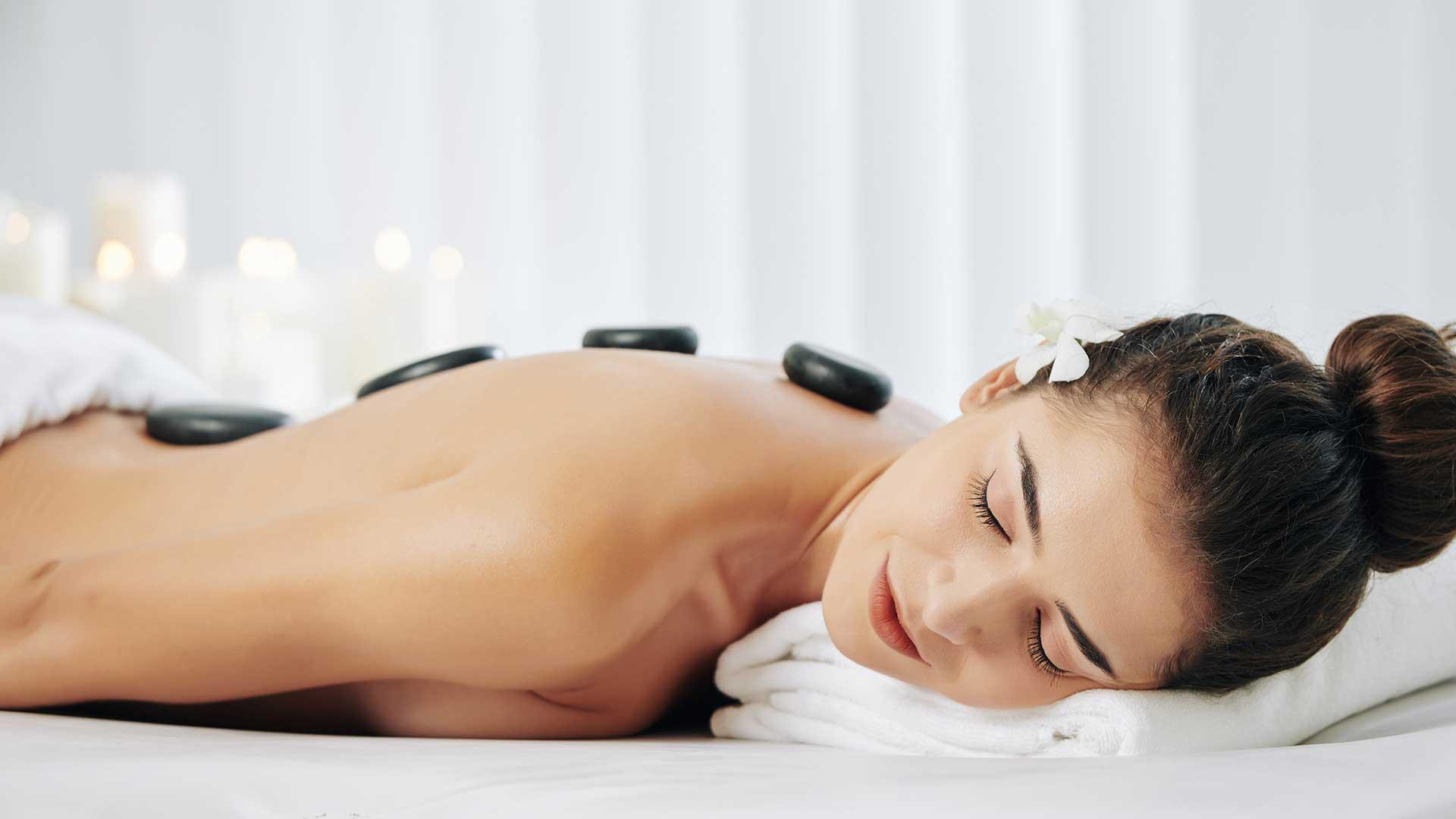 Frau liegt entspannt bei einer Hot & Cold Stone Massage auf der Liege