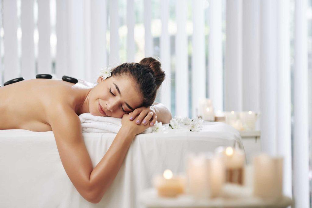 Frau liegttiefenentspannt bei Hot & Cold Stone Massage auf der Liege