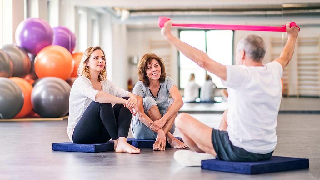 Ein Mann und zwei Frauen beim Training mit Theraband für Rückentraining
